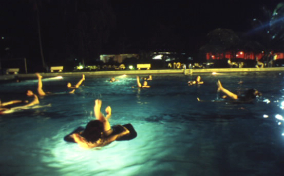"Western expatriates take a break from humanitarian relief operations to practice ""aquatic yoga"" at a plush club swimming pool off limits to ordinary Congolese people. Just one of the many perks of relief work in ""exotic"" foreign war zones. – Photo: Keith Harmon Snow, 2007"