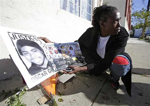 Lovelle Mixon's cousin Dolores Darnell holds pictures of family members who have been killed and a poster of Oscar Grant on Monday, March 23, outside the apartment building where Lovelle was killed. – Photo: Eric Risberg, AP