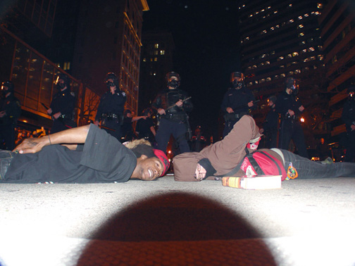 """Tensions have remained high since war in Oakland broke out at 2 a.m. on New Year's when BART police murdered Oscar Grant. Here, during the first rebellion, on Jan. 7, young people taunt the cops by lying face down, assuming Oscar's position when he was executed, in a pose that conveys the message, """"We are all Oscar Grant."""" – Photo: Dave Id, Indybay"""
