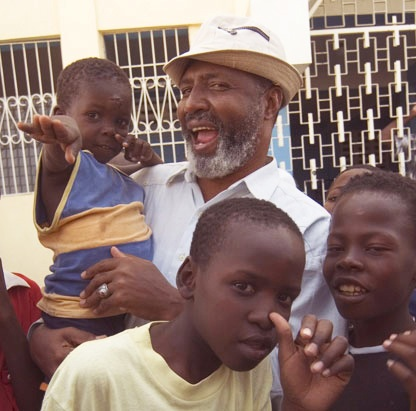 """Jesus-like revolutionary priest Father Gerard Jean-Juste """"suffered the little children to come unto him,"""" tending to their needs, body and soul, and fighting for their future and for justice in Haiti."""
