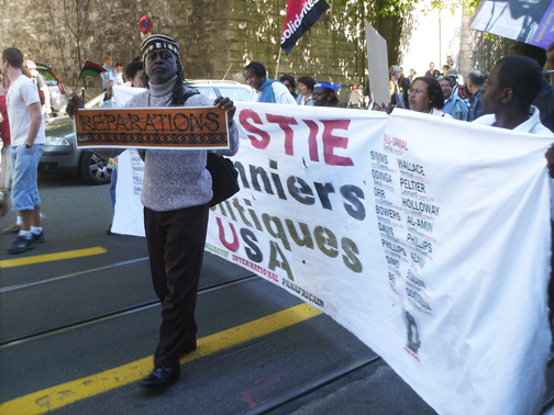 At the Durban Review Conference, backed by a banner designed by legendary Black Panther artist Emory Douglas, Brother Jahahara marches with the International Pan Afrikan Collective through the streets of Geneva.
