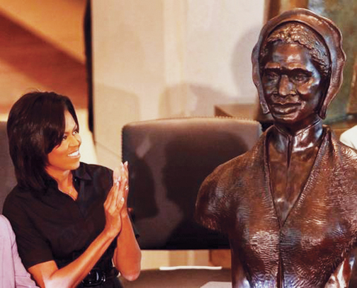 """Michelle Obama applauds during the unveiling April 28 of the bust of Sojourner Truth in Emancipation Hall of the U.S. Capitol in Washington. """"I hope that Sojourner Truth would be proud to see me, a descendant of slaves, serving as the first lady of the United States of America,"""" Obama said. """"Now many young boys and girls, like my own daughters, will come to Emancipation Hall and see the face of a woman who looks like them."""" - Photo: Manuel Balce Ceneta, AP"""