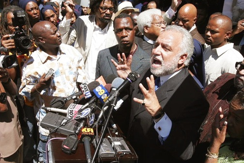 Danny Bakewell (speaking) holds a press conference Aug. 26, 2005, to condemn police terrorism the day after Minister Tony Muhammad (center with swollen face) was badly beaten by LAPD at a street vigil. Three years later, Min. Tony won a $140,000 settlement from the city.