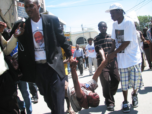"""Angry mourners carry the body of """"Ti Charles"""" from Port-au-Prince Cathedral to the Presidential Palace after U.N. troops fired on Jean-Juste funeral goers. The boy on the right is wearing one of thousands of memorial T-shirts with the famous picture of Father Gerry looking out from behind bars that were distributed by activists from Veye Yo, the organization he founded in Miami. – Photo: Haiti Liberté"""