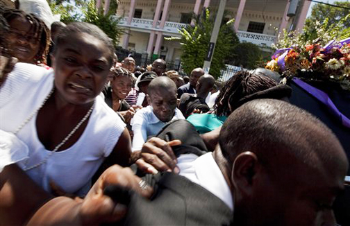 Mourners flee as gunshots are fired at the funeral procession for Father Gerard Jean-Juste in Port-au-Prince, Thursday, June 18. A man was shot in the head and killed as unrest swelled.  Photo: Ramon Espinosa, AP