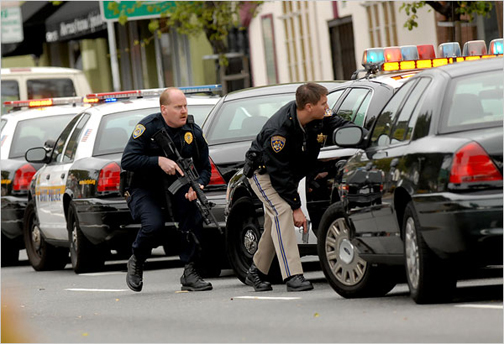 """On March 21, 2009, in East Oakland, the day Lovelle Mixon died along with four Oakland police, these officers were part of the manhunt to find Lovelle after the two officers who had encountered him during a """"routine traffic stop"""" were killed. – Photo: Dan Rosenstrauch, Bay Area News Group/AP"""