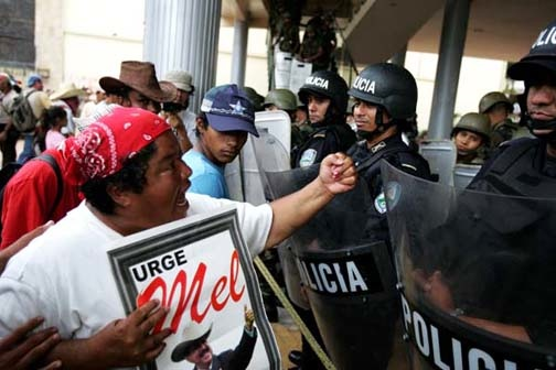 A Black Honduran woman shakes her fist at riot police protecting the coup government July 15.