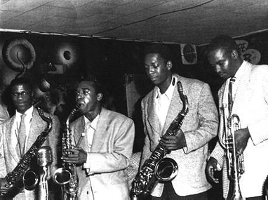 Fillmore in '50s – before it was bulldozed by the Redevelopment Agency – was Black and thriving and known worldwide as Harlem of the West. Here are John Handy, Pony Poindexter, John Coltrane and Frank Fischer at Bop City.