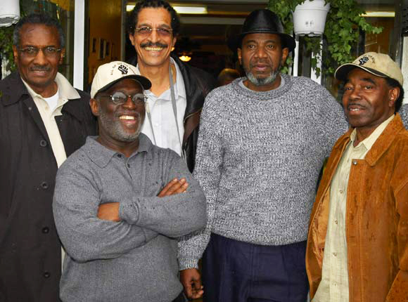 "John Bowman, backed here by Hank Jones, Ray Boudreaux, Harold Taylor and Richard Brown of the SF 8, would have been arrested with them if he hadn't died the month before. One of the three who were tortured by New Orleans police in 1973 at the behest of San Francisco police, he said in the film, ""Legacy of Torture"": ""The same people who tried to kill me in 1973 are the same people who are here today, trying to destroy me. I mean it literally. I mean there were people from the forces of the San Francisco Police Department who participated in harassment, torture and my interrogation in 1973 ... None of these people have ever been brought to trial. None of these people have ever been charged with anything. None of these people have ever been questioned about that."" – Photo: Scott Braley"