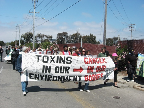 After demanding that PG&E properly clean up the Hunters Point Power Plant, participants began their march to Parcel A of the Hunters Point Shipyard. Marie Harrison's grandson, Roman, a veteran of the struggle for environmental justice, enthusiastically led the group. Children in Bayview Hunters Point, who suffer the most from environmental toxins and additionally from poverty when their parents are refused jobs in the cleanup, know that holding Lennar, PG&E and City Hall accountable requires constant pressure from the people. – Photo: Chris Brizzard