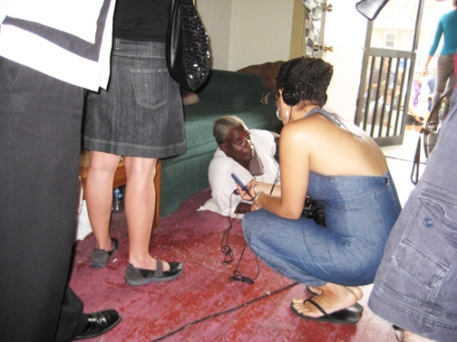 Naomi Burkhalter, a former renter who has been priced out of the rental market and is currently taking shelter in an abandoned home, is reclining on the floor because of a leg injury due to living in poor conditions as she is interviewed by U.N. advisors. – Photo: Eric Tars