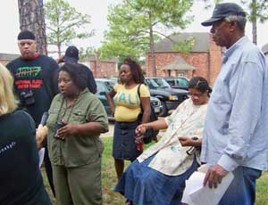 Katrina survivor Eugenia Brown speaks to the press about intolerable housing conditions in Houston tolerated by FEMA as her neighbors, survivors Quinna Brown and Jennifer Whittington, and legendary housing advocate Lenwood Johnson look on. - Photo: Gloria Rubac