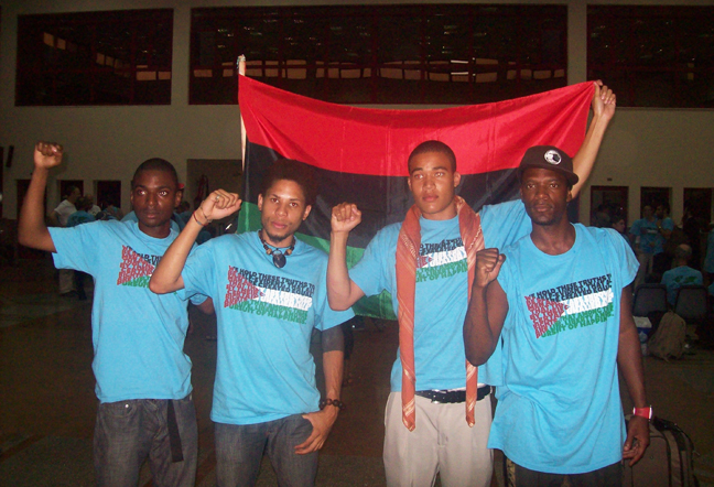 """M1, shown here with young Black members of the Viva Palestina Caravan, writes in Part I: """"I felt extremely proud when the brothers got together to wave our red, black and green Liberation flag in the immigration office [at the Egyptian border] as they chanted loud enough for the people to hear us on the other side in Gaza."""""""
