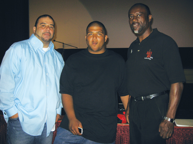 At Oakland's Grand Lake Theater on Aug. 20, at the kickoff of Cynthia McKinney's Triumph Tour, an update on the Oscar Grant case from the family's perspective was an important part of the program. Here, Jack Bryson, his son Jackie and Oscar Grant's Uncle Bobby pose for Bay View Arts Editor Wanda Sabir. – Photo: Wanda Sabir