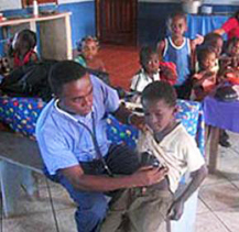 Dr. Luther Castillo treats a young patient at the Garifuna Community Hospital, which he led the community to build. It was shut down by the coup government on Oct. 7.