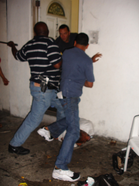 Police raided Juanita Young's home during a cookout Aug. 8. Here, one cop swings a metal baton at one son while another son, JJ, badly beaten and bloody, lies at the cops' feet. – Photo: Kathie, October 22nd, NYC Indymedia