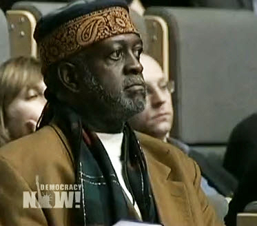 "Baba Jahahara, who is covering the UN climate summit for the SF Bay View, is shown on Wednesday's Democracy Now listening to U.S. chief negotiator Todd Stern, whom he had challenged earlier, reject reparations to save and restore the homelands of those hardest hit by climate change who took no part in creating it. Stern said, ""We fully recognize our historic role in putting emissions up in the atmosphere, and we also recognize our responsibility to be part of an overall global effort to help poorer countries, both with regard to the need to adapt to the effects of climate change and the need to help them develop a sustainable path, which at this point in our collective history means a low carbon path. Reparations to me conveys a sense of culpability, guilt, that kind of thing. I don't think that's a legitimate way to look at it."" – Video frame: Democracy Now!"