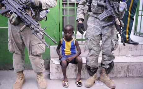 Haiti-earthquake-boy-sits-outside-PAP-hospital-between-2-US-soldiers-012010-by-EPA, Earthquake in Haiti: Under Aristide, Haitians were prepared for disaster, World News & Views