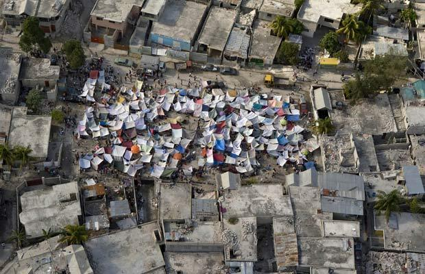 Haiti-earthquake-sheets-shield-from-90-degree-heat-011310-by-Getty-Images, Shades of Katrina: No help for Haitians who need it most, World News & Views