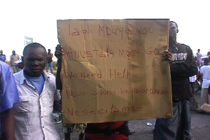 Haiti-earthquake-sign-'The-rain-has-soaked-us.-MINUSTAH-UN-must-go.-We-need-help.-We-need-aid'-PAP-021110-by-HIP, Protesters clash with police following rain in Haiti, World News & Views