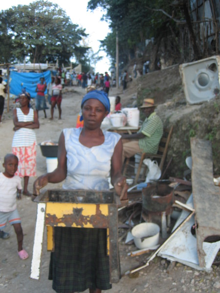 Haiti-earthquake-woman-made-salvaged-metal-into-stove-PAP-020810-by-Flavia-Cherry, Haiti from the front lines: Genocide by omission, World News & Views