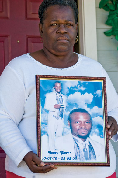 Edna Glover holds a portrait of her son, Henry, whose charred body was found behind a police station. – Photo: Chandra McCormick and Keith Calhoun, The Nation