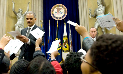 """Department of Justice employees ask their new boss, Attorney General Eric Holder, to autograph their Black History Month programs after he delivered this speech urging """"a nation of cowards"""" to begin confronting the issue of racial justice. – Photo: Saul Loeb, AFP-Getty Images"""
