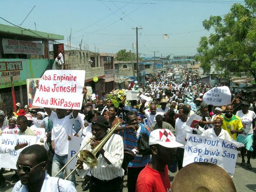 Marching with blaring trumpets and chanting crowds on Jan. 26, 2008, Haitians say No to the U.N. massacres in the Site Soley neighborhood of Port au Prince. Ever since enslaved Haitians defeated Napoleon's armies in 1804 to become the world's first independent Black nation, world powers have tried to kill the bodies and spirits of their descendants. But, defiant and resilient, Haitians march on. – Photo: Jean Ristil, HaitiAnalysis.com