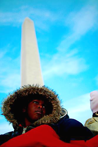 From the base of the Washington Monument, a boy watches and waits for the inauguration to begin. – Photo: Mario Tama, Getty Images