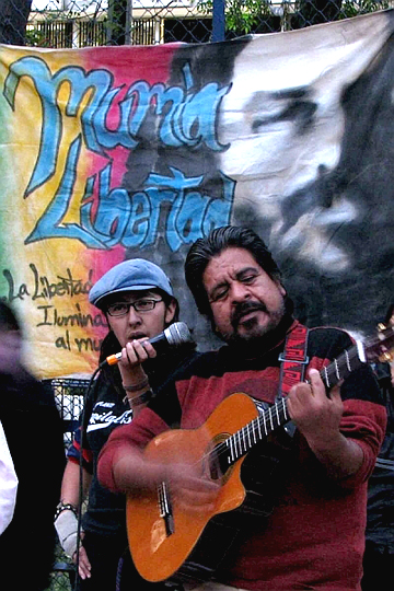At the U.S. Embassy Dec. 9, Jorge Salinas sang in solidarity with Mumia, holding his guitar in arms once paralyzed and playing with hands once fractured in Atenco.