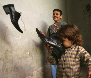 Outside Muntather al-Zaidi's apartment in Baghdad, children play with another pair of his shoes. The older boy may be the 6-year-old nephew who said he'd throw these shoes if his uncle is not released. – Photo: Hadi Mizban, AP
