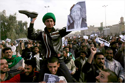 In solidarity with Al-Baghdadia TV journalist Montather Al-Zaidi, a young man, held aloft by his friend during a protest in Najaf Monday, holds a shoe in one hand and a caricature of Bush in the other. - Photo: Alaa Al-Marjani, AP