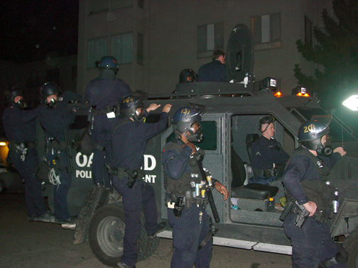 """Davey asks, """"Was this exaggeration of damage an excuse to justify the police bringing out what looked like a small army tank coupled with scores of police who outnumbered the protestors?"""" Nearly all the police out on the streets on Jan. 7 were white. The officer in the foreground here is an exception. – Photo: Dave Id, IndyBay"""
