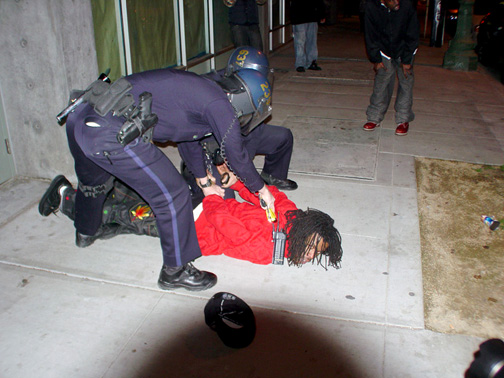 """Oakland police arrests on Jan. 7 were unnecessarily brutal. The photographer who took this picture wrote: """"This guy was walking with a group of friends about a half block past McDonald's on 14th when police targeted just him and chased him in a circle back around the McDonald's. He then ran across the street and once he saw there were cops running at him from both sides, he just stopped and stood there. Cops pushed him down and immediately began tasering him as he lay there not resisting. They may have tasered him for close to a full minute. Since when did using tasers become a standard part of handcuffing someone?"""" – Photo: Dave Id, Indybay"""