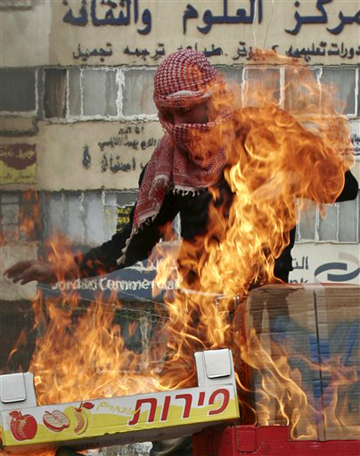 """An Israeli Palestinian burns Israeli produce boxes during a protest. """"Whenever Israel has been in conflict with its neighbors, the allegiances of its Arab citizens have been tested, and their empathy has often been with the other side,"""" according to the New York Times Jan. 19. """"But this war was worse, they say, because it was waged against their own people and they were watching it as it happened. More prosperous, educated and 'Israeli-fied' than their kin in the West Bank and Gaza, the Israeli Arabs are becoming more Palestinian at the same time. The feelings of estrangement could last long after the Gaza war."""" – Photo: AP"""