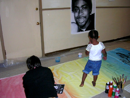 Poor's fun raiser mural painting party on Saturday, Jan. 10, to bless their new headquarters with great art was truly multi-generational. This barefoot baby artist probably knows that the last words of Oscar Grant, whose photo is on the wall, were a plea for his life as a loving father to his daughter, a little girl just like her. – Photo: PNN